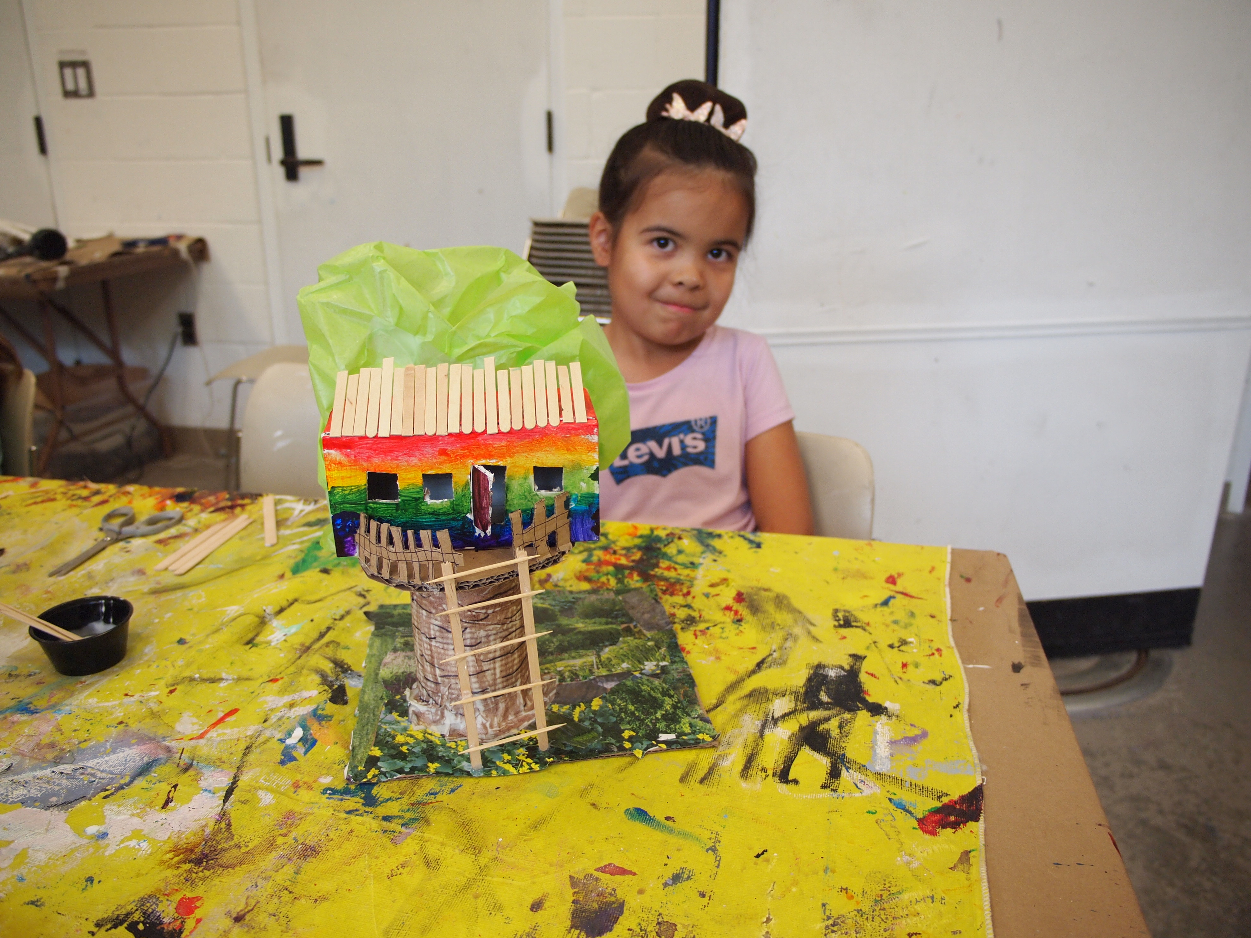 A young girl in a pink Levi's t-shirt smiles while seated behind a mixed-media treehouse sculpture resting on a paint-covered yellow tablecloth