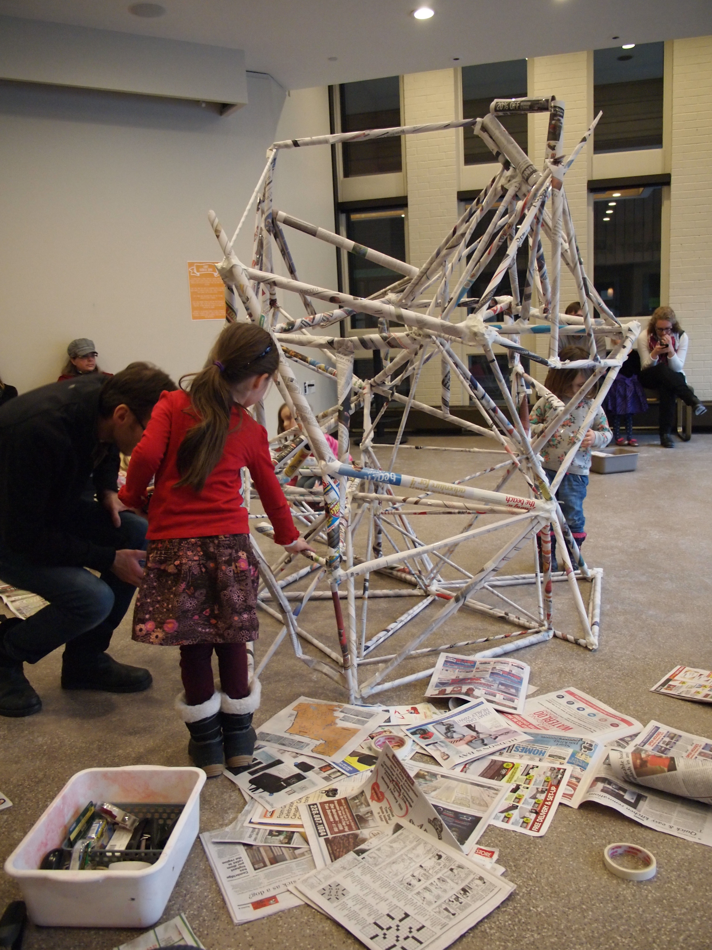 A child works on creating a large papier mache sculpture that fills the centre of the activity space.