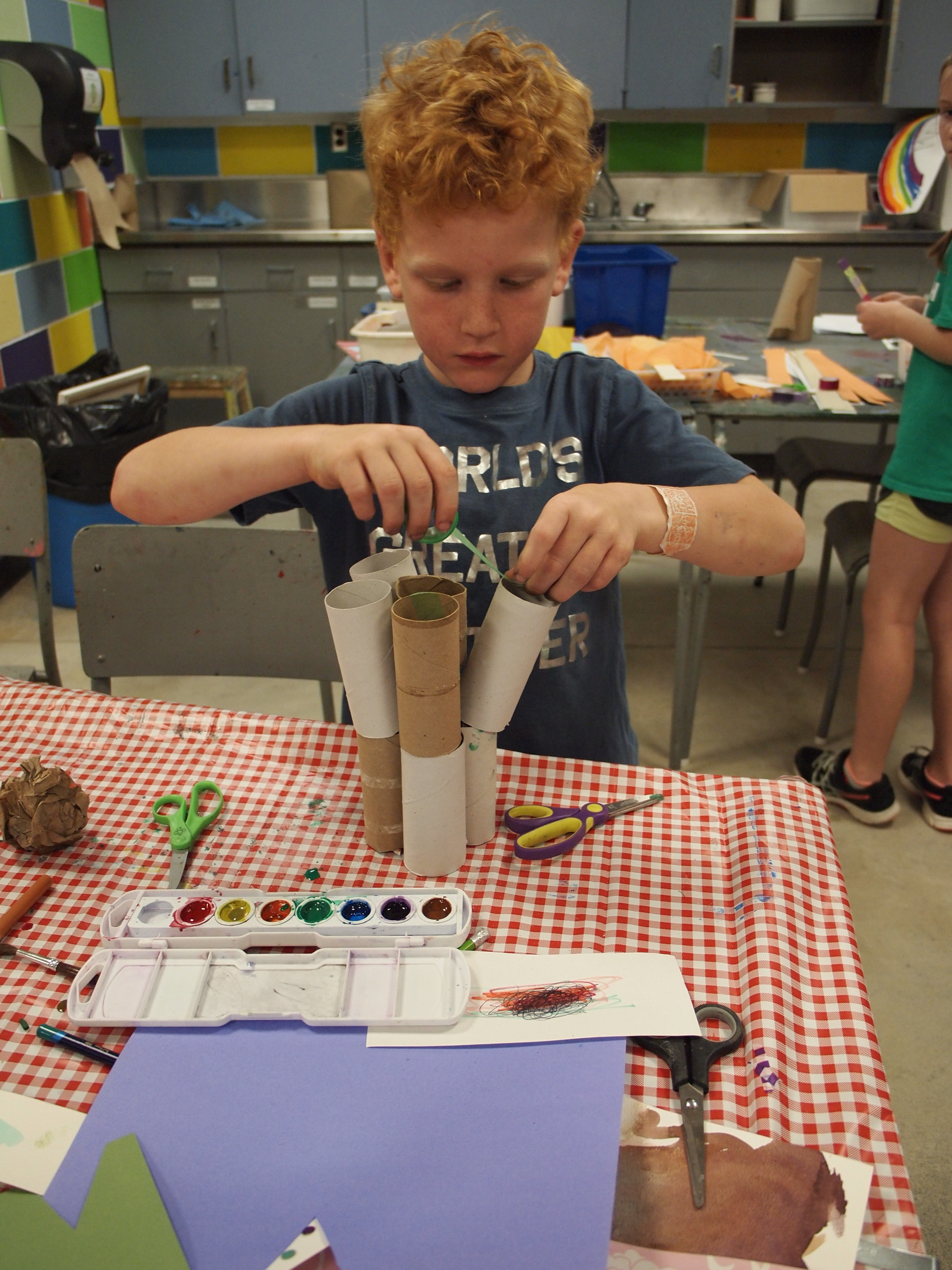 A small boy assembling a sculpture from paper rolls in the KWAG studio