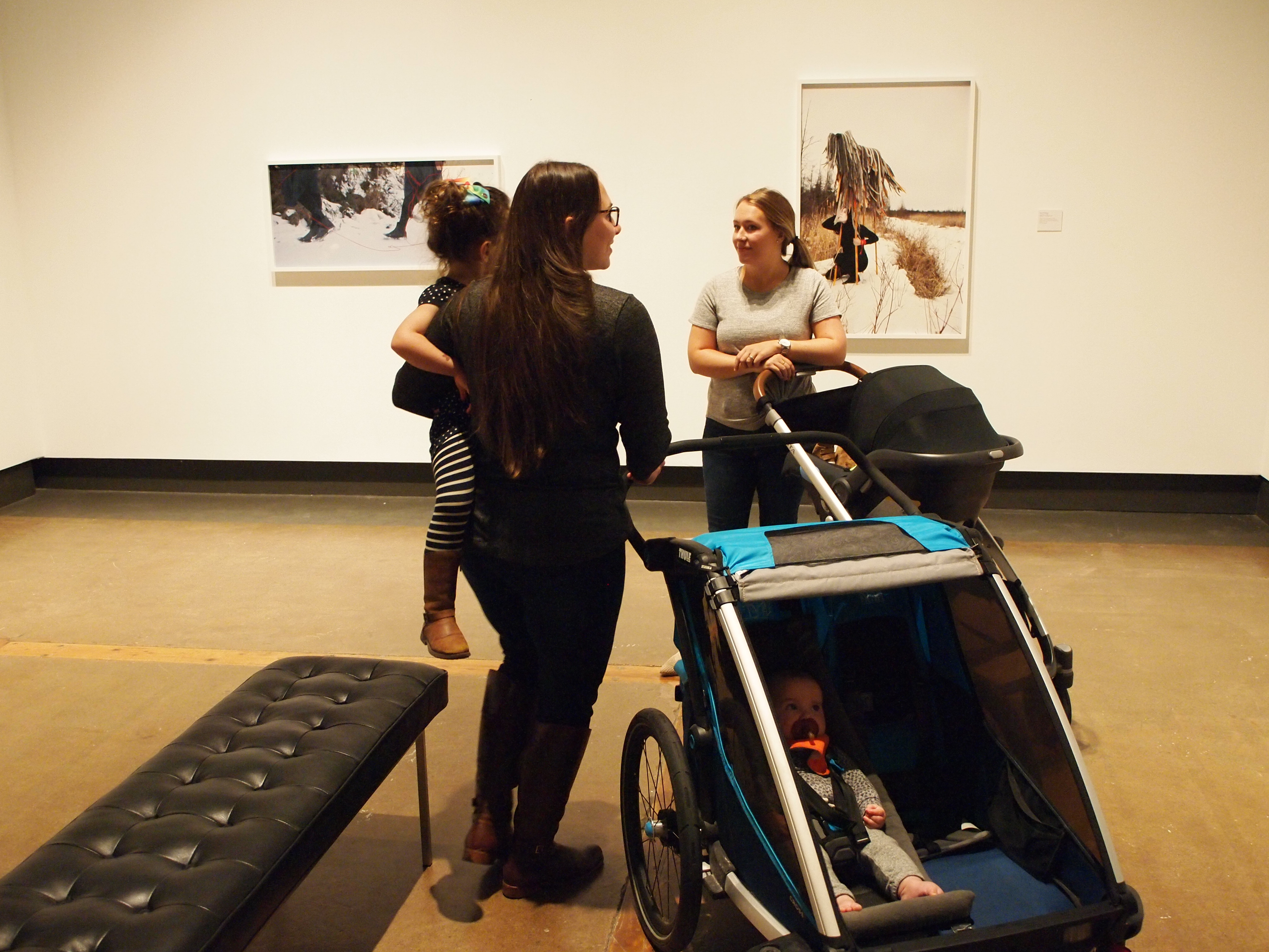 Two mothers with strollers carrying young babies smiling and chatting together in the gallery