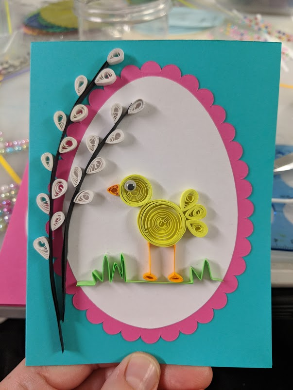 A handmade card with a baby chick and pussywillows against an egg-shaped background showing various paper quilling techniques