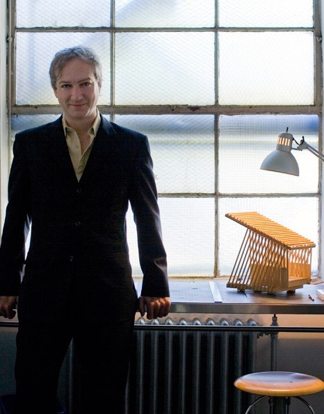 Photo of Paul Raff, an unusually pretty older man in a dark suit and open-collar beige shirt leaning against a windowsill in an industrial building; a small architectural model sits on the sill next to him
