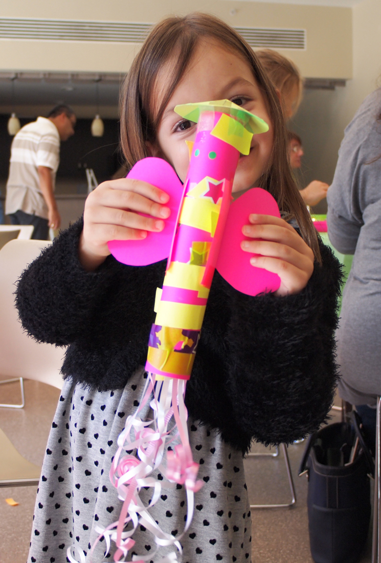 A young girl in concert dress holds up a large, colourful construction paper rocket at a recent Pre-Concert Experience