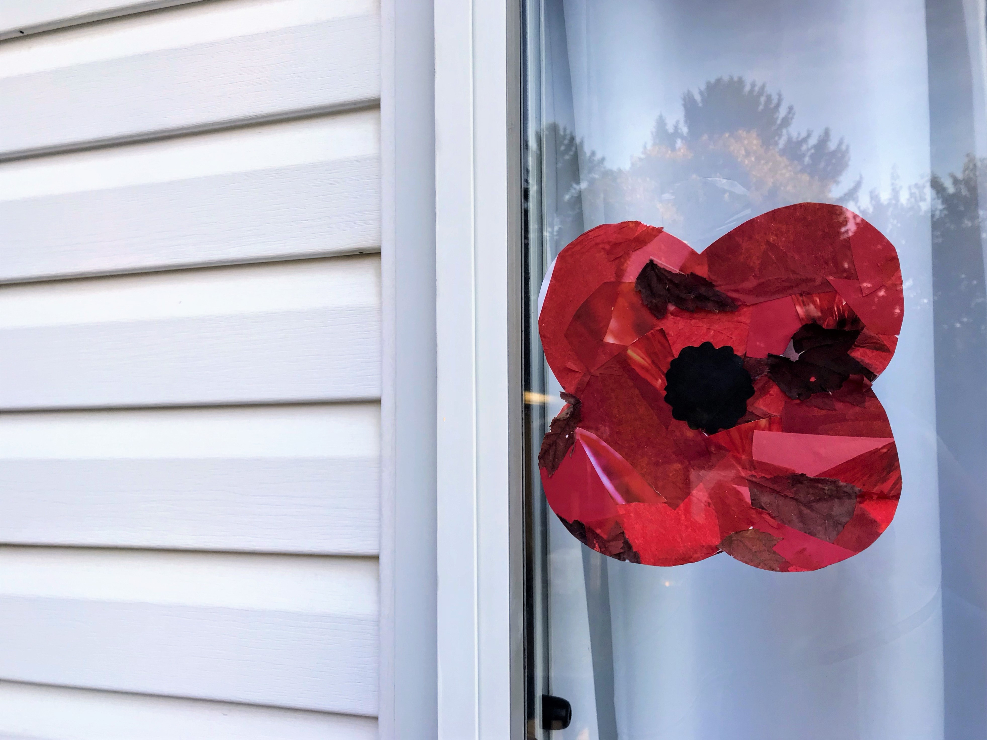 Photo of a red collaged poppy with a black centre displayed in the window of a house with white aluminum siding