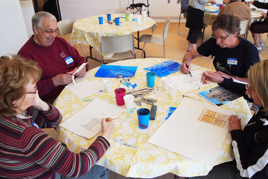 A group of four seniors creating art at a round table