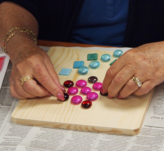 Close-up image of an elderly woman's hands as she arranges glass beads and tiles on a wooden substrate