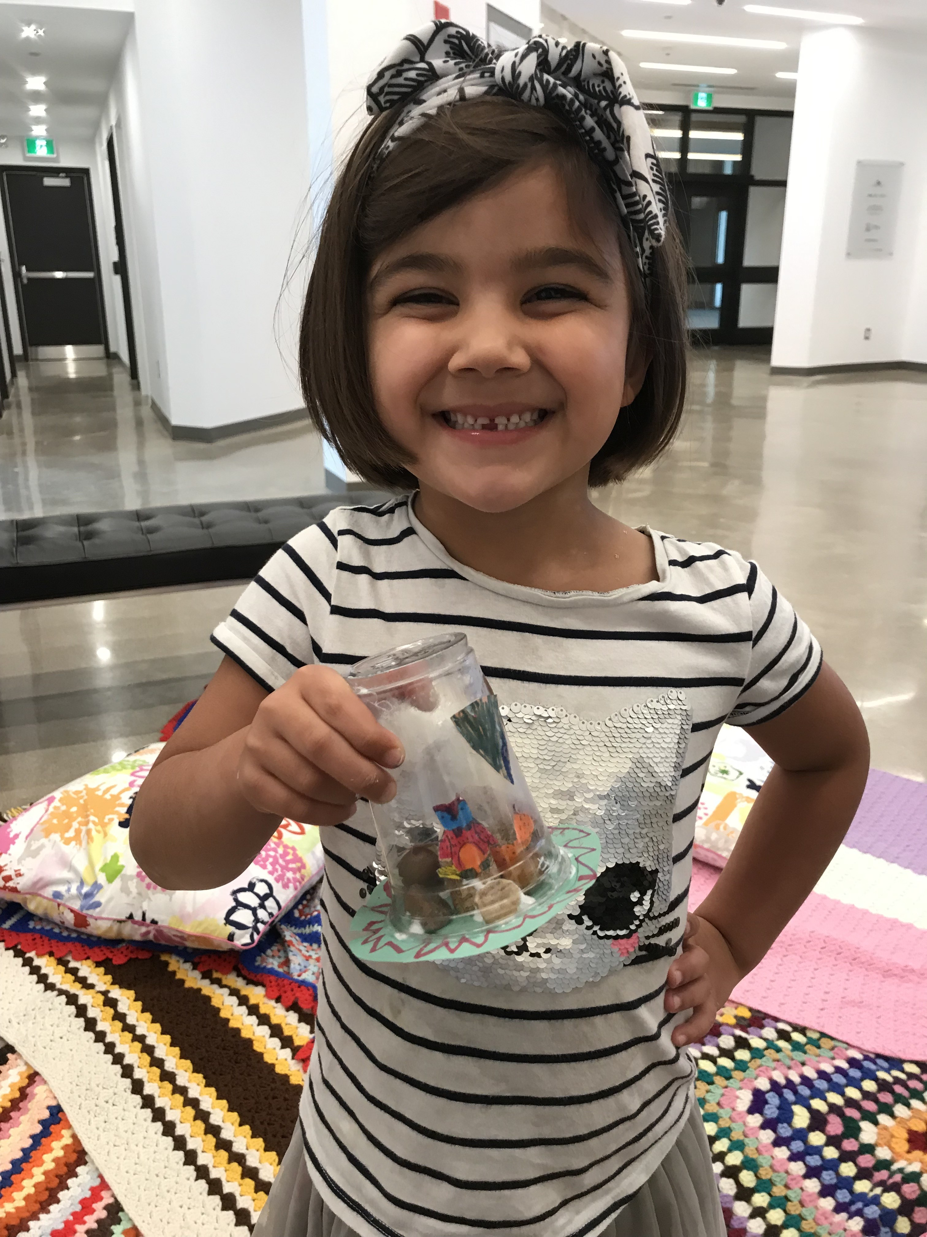 A young girl smiling as she shows off a mini terrarium made from found materials at Family Sunday