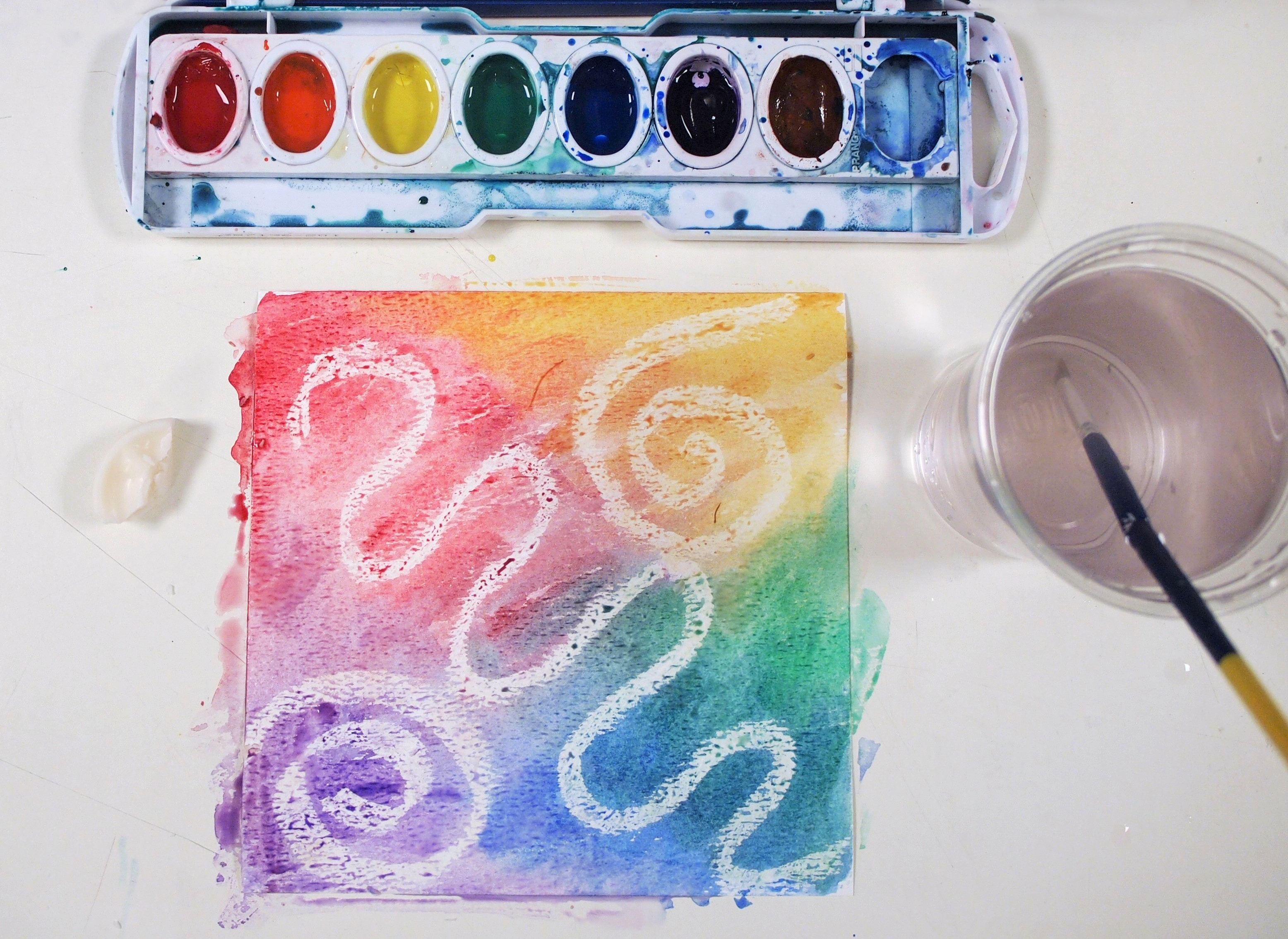 Overhead photo of a colourful watercolour abstract alongside a cup of rinse water and a watercolour palette