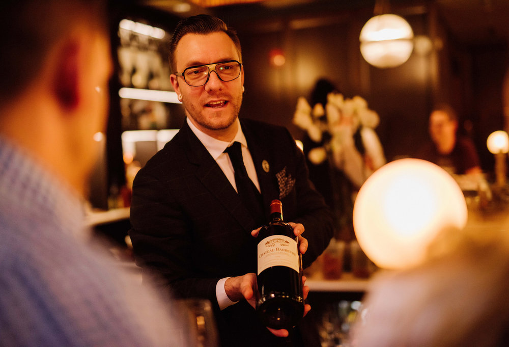 Photo of Wes Klassen, a well-dressed man in contemporary glasses presenting a bottle of wine in a warmly-lit restaurant setting