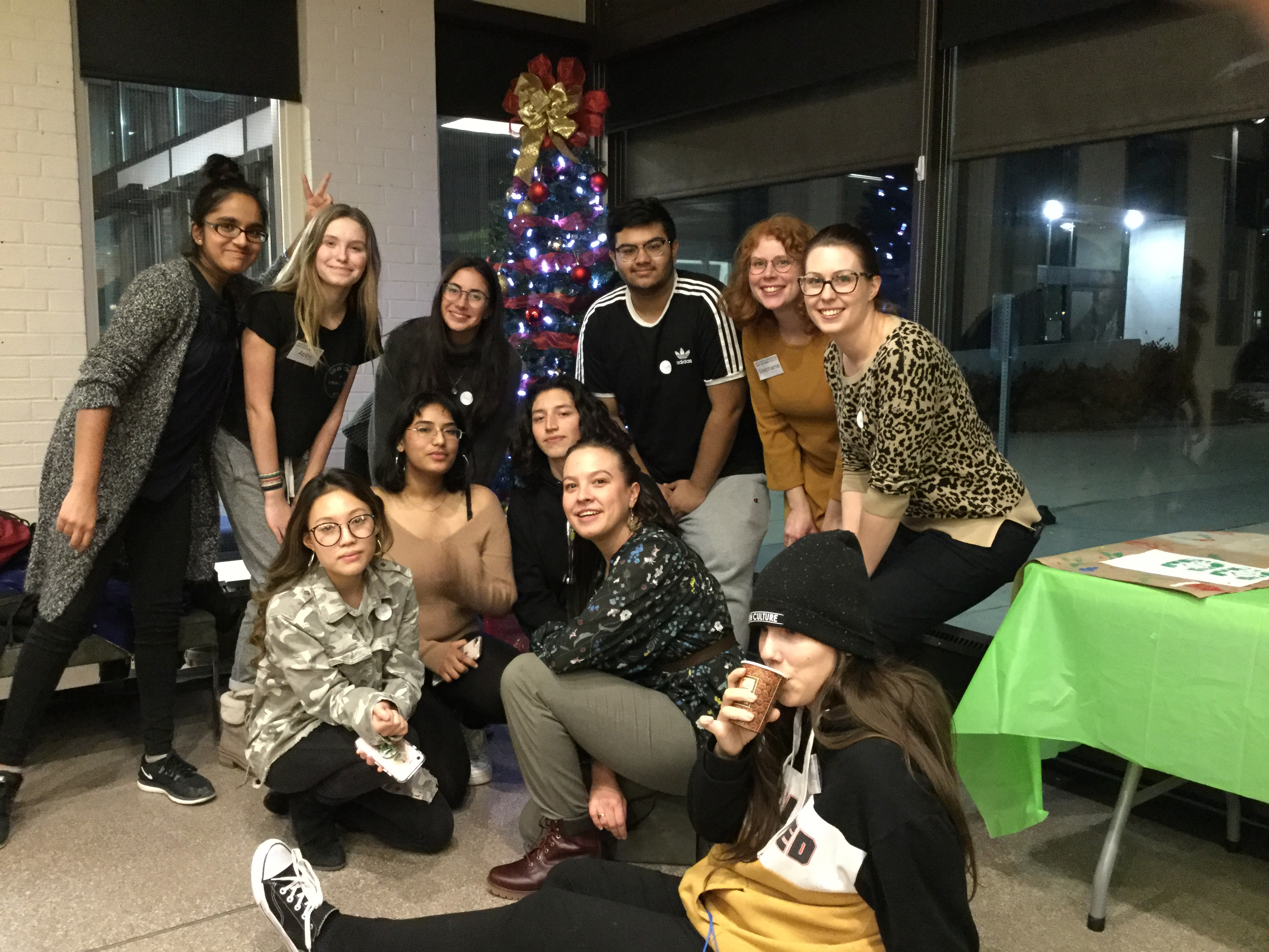 Photo of Youth Council members posing in front of a Christmas tree at the winter holiday party
