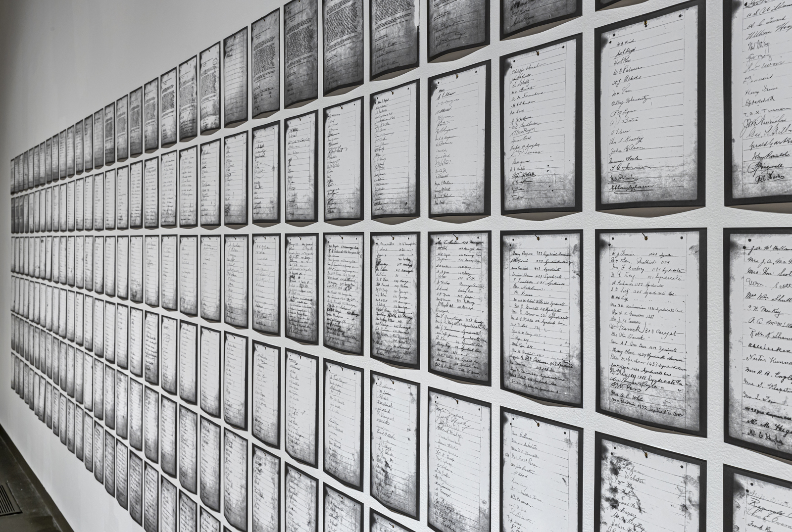 Installation view of Deanna Bowen's installation of a photocopied petition arranged in long rows on a gallery wall