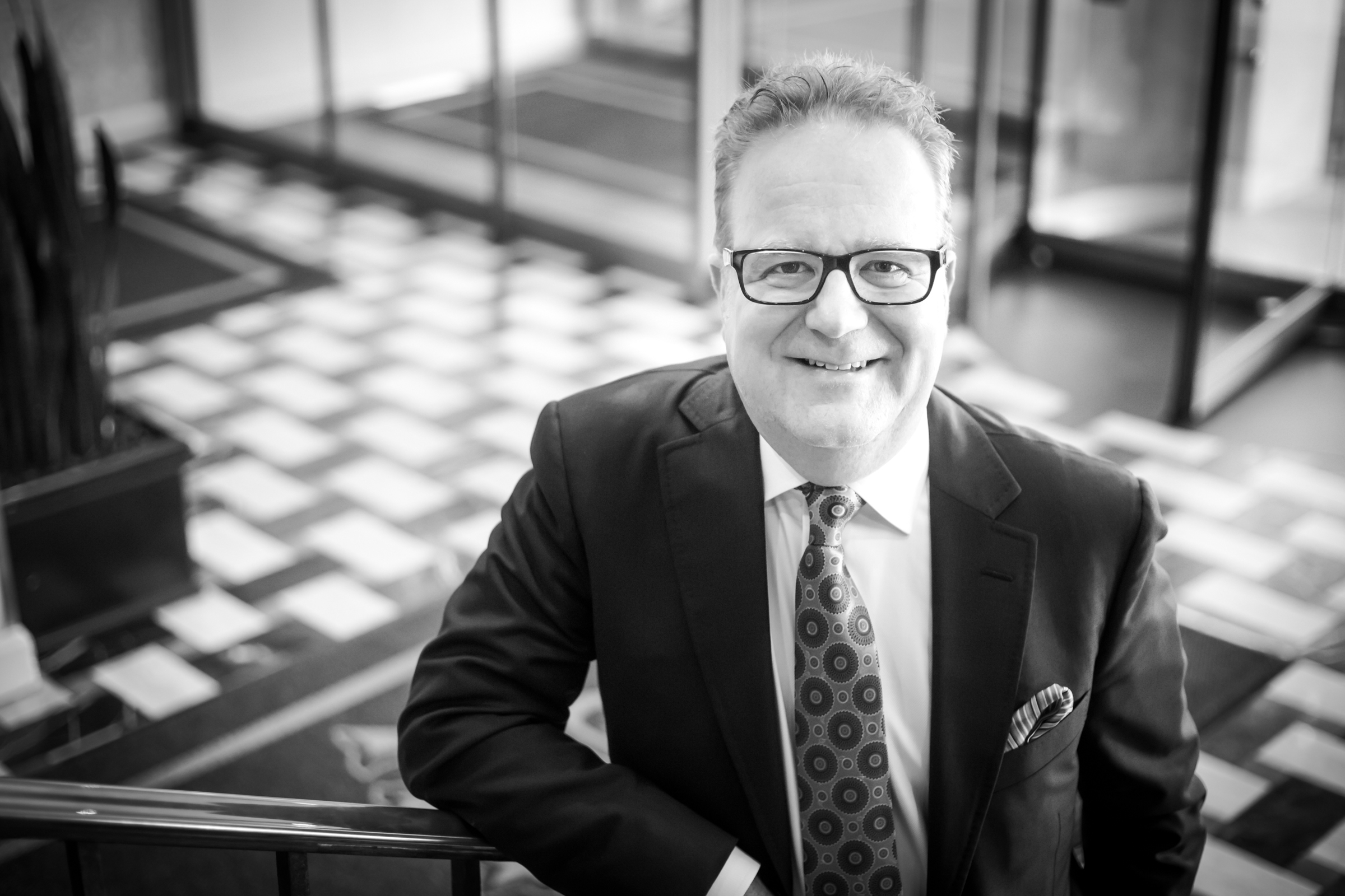 Black and white photograph of Allan Bush, a smiling man in suit and glasses standing partway up a staircase with a tiled lobby visible in the background