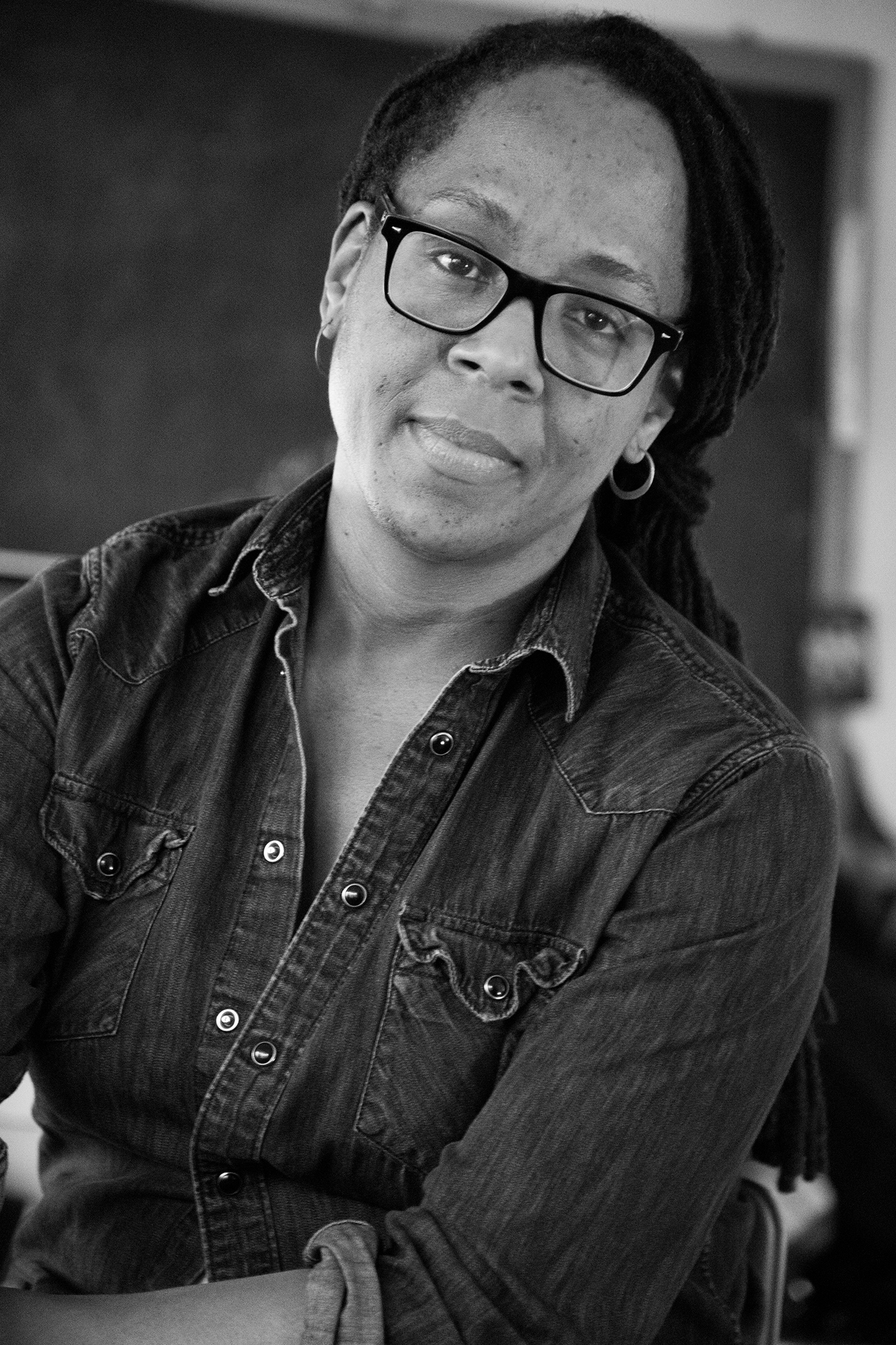 Black and white photo of Deanna Bowen, a Black woman with dark-rimmed glasses, small hoop earrings and long black hair pulled back in braids wearing a button-down denim shirt