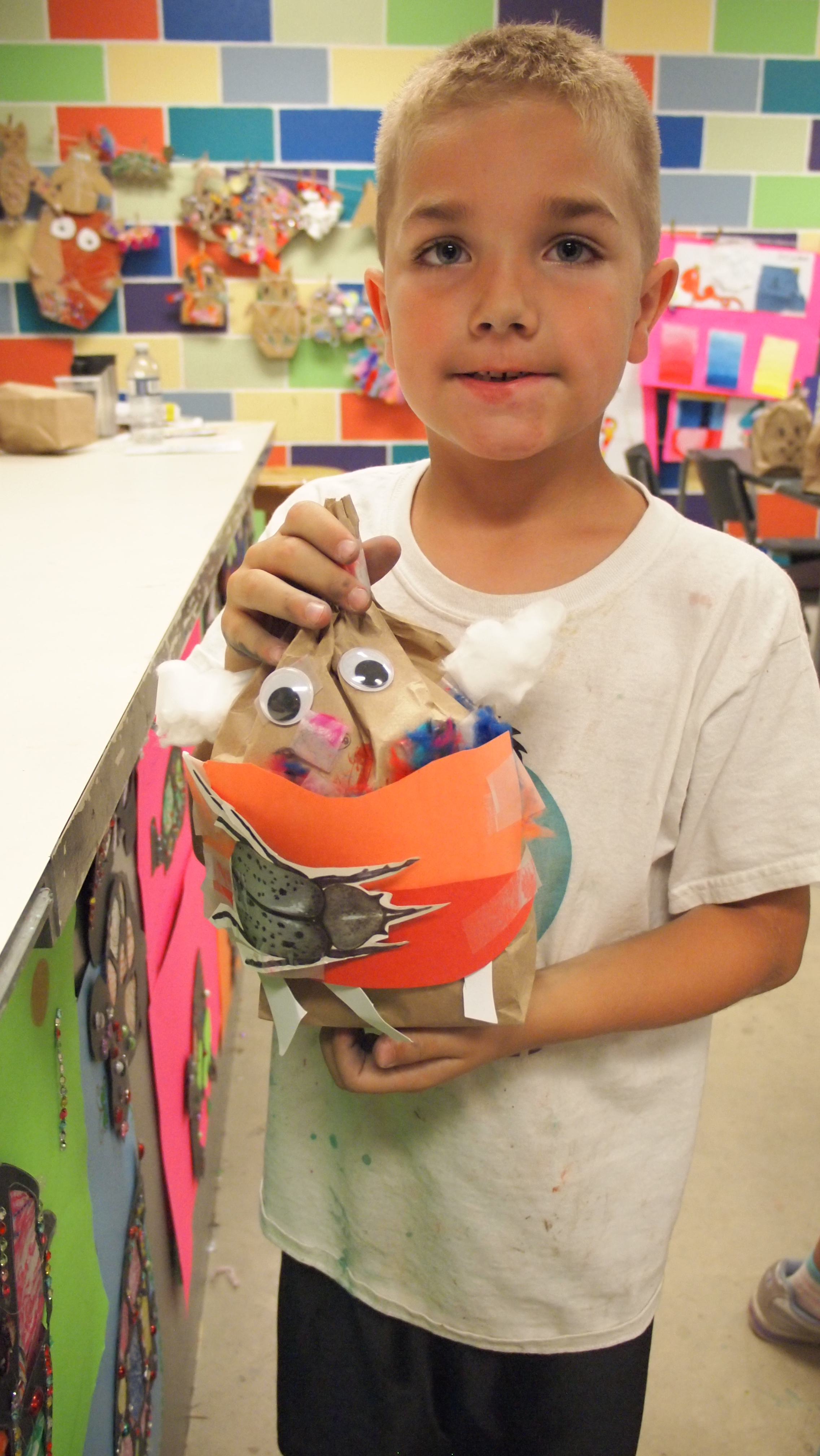 Photo of young boy holding up a mixed media creature sculpture