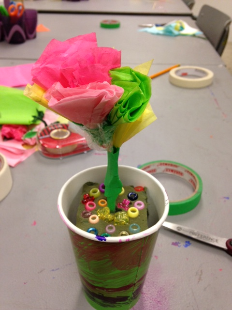 A tissue paper flower sits upright in a painted paper cup supported by foam and beads