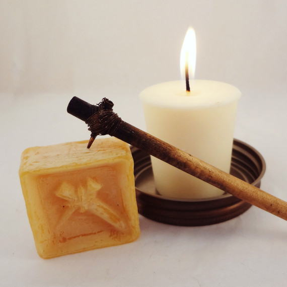 A block of wax and decorating tool displayed alongside a lit white pillar candle