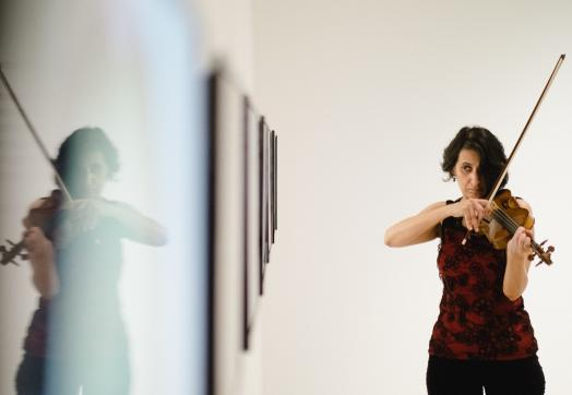 A woman violinist in dark clothing plays her instrument while reading from a series of framed artworks seen from a long side angle