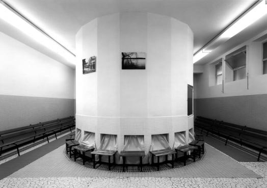 A black and white Lynne Cohen photograph of a tiled spa interior dominated by a round white structure that fills the low-ceilinged space