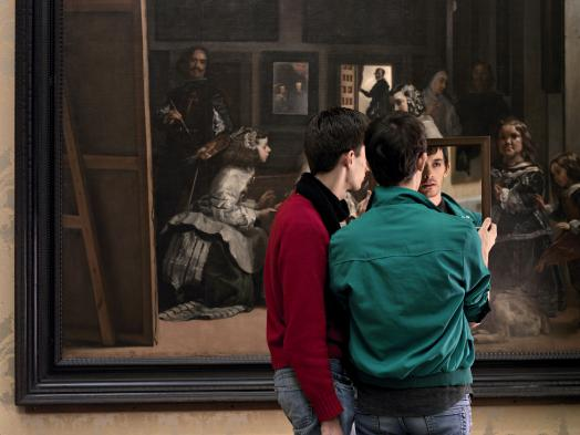 Two Mirrors by Adad Hannah shows two young men holding up a mirror to their own reflections while standing before Velazquez' painting Las Meninas