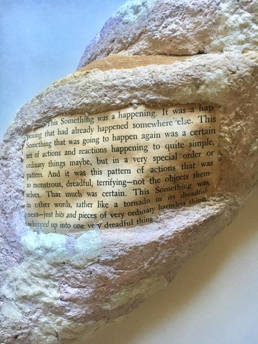 Close up image of a rock formation made from paper pulp embedded with a legible page of text from a yellowed trade paperback book