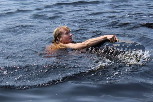 Woman swimming in water with giant black comb