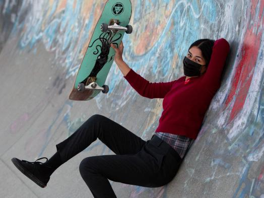 A female skateboarder in dark clothes and a black facemask holds up her green skateboard while reclined against the side of a graffiti-covered half-pipe wall
