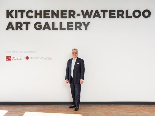 Photo of Allan Bush, an older man in a dark suit and glasses, standing alongside signage recognizing Free Admission Sponsor CIBC Wood Gundy - Allan Bush Investment Team