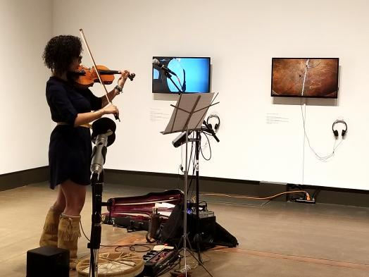 Charlena Russell playing violin next to two video screens featuring Peter Morin's NDN Love Songs