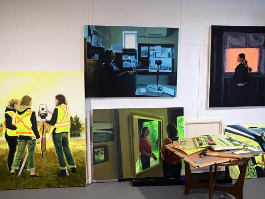 View of Amanda Rhodenizer's studio wall showing four paintings in progress of working women in saturated colour settings; a small studio table sits in the foreground