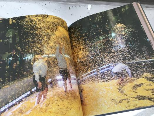 Photo of a book open to a double-page spread photo of three people reveling in a cloud of gold confetti