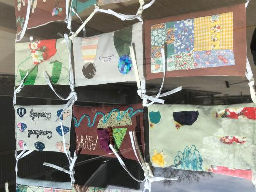 Portion of a community quilt made of face masks tied together, each illustrated with textiles and painting, on view behind a glass window