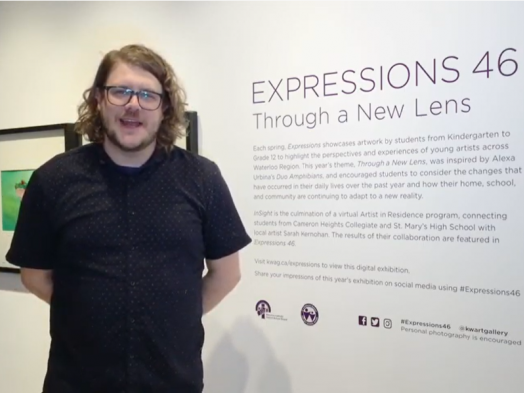Screenshot of Steve Lavigne, a man with curly shoulder-length hair in a short-sleeved black shirt, standing in front of a didactic wall for Expressions 46: Through a New Lens