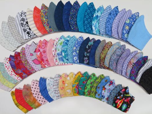 Three rows of homemade face masks arrayed in a spectrum of colours and patterns