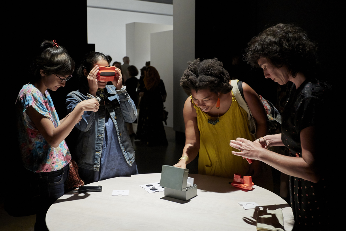 Four women look through Viewmaster slides in Aislinn Thomas' installation at KWAG in 2018