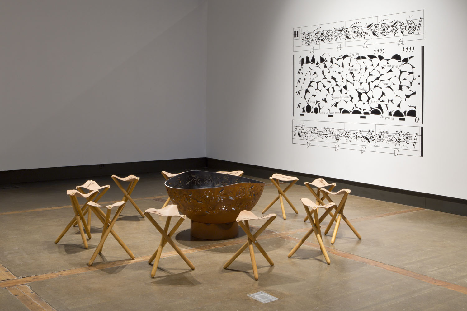 Installation view of Surrounded/Surrounding, a circular arrangement of leather stools around a copper fire bowl etched with a floral pattern, in front of a white gallery wall with a black vinyl transfer of a large pattern of shapes and text