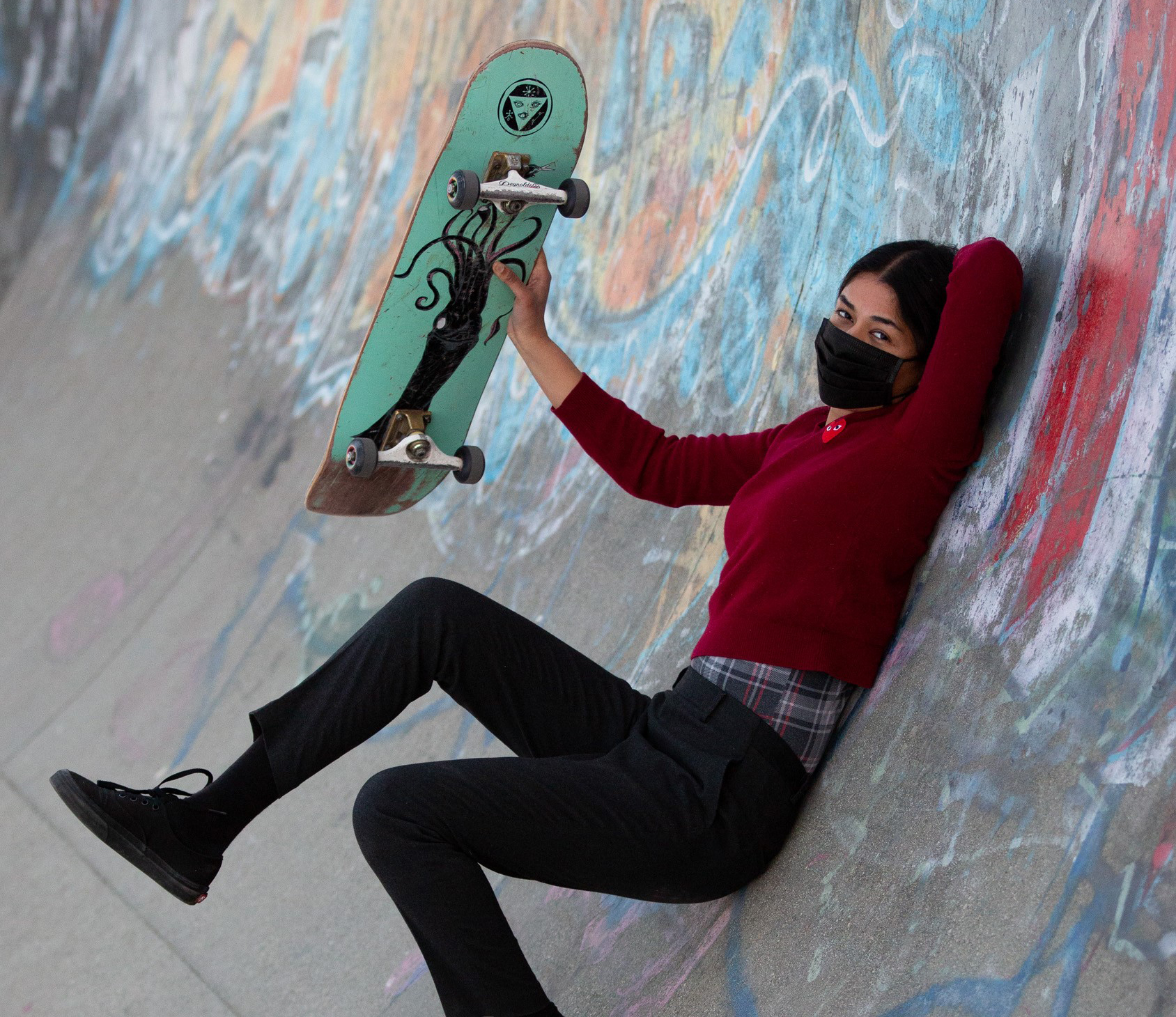 Adad Hannah photograph of a female skateboarder in a black face mask reclining in a graffit-covered half-tube