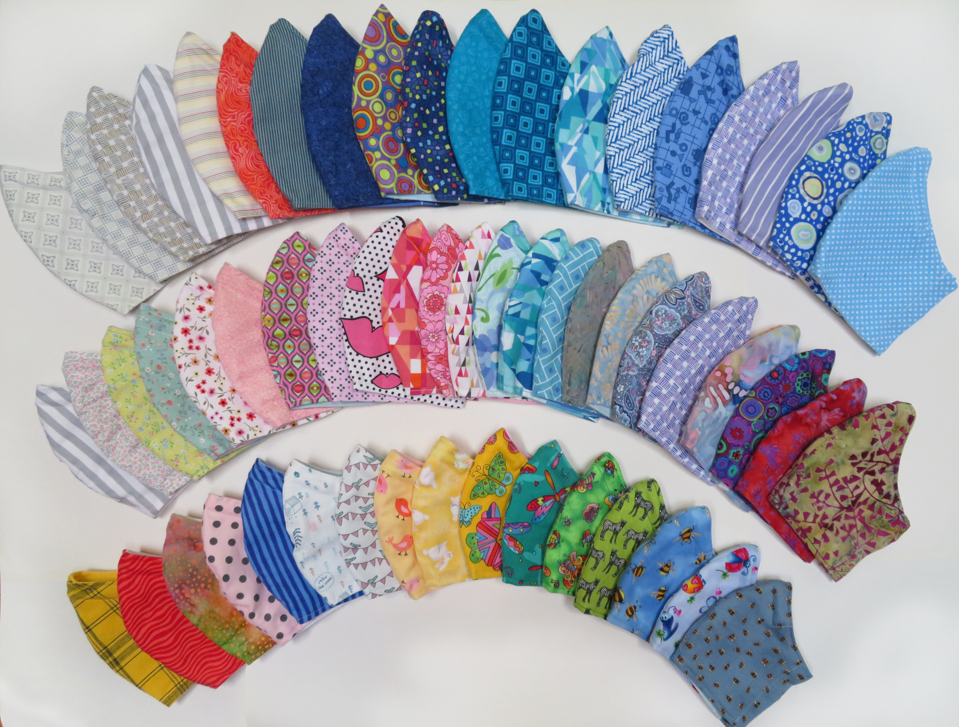 Face masks laid flat in three arcing rows to show range of colours and patterns