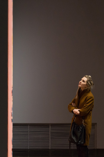 A woman gazes up at a large painting, unseen except for the edge of its canvas, in a darkened gallery at KWAG