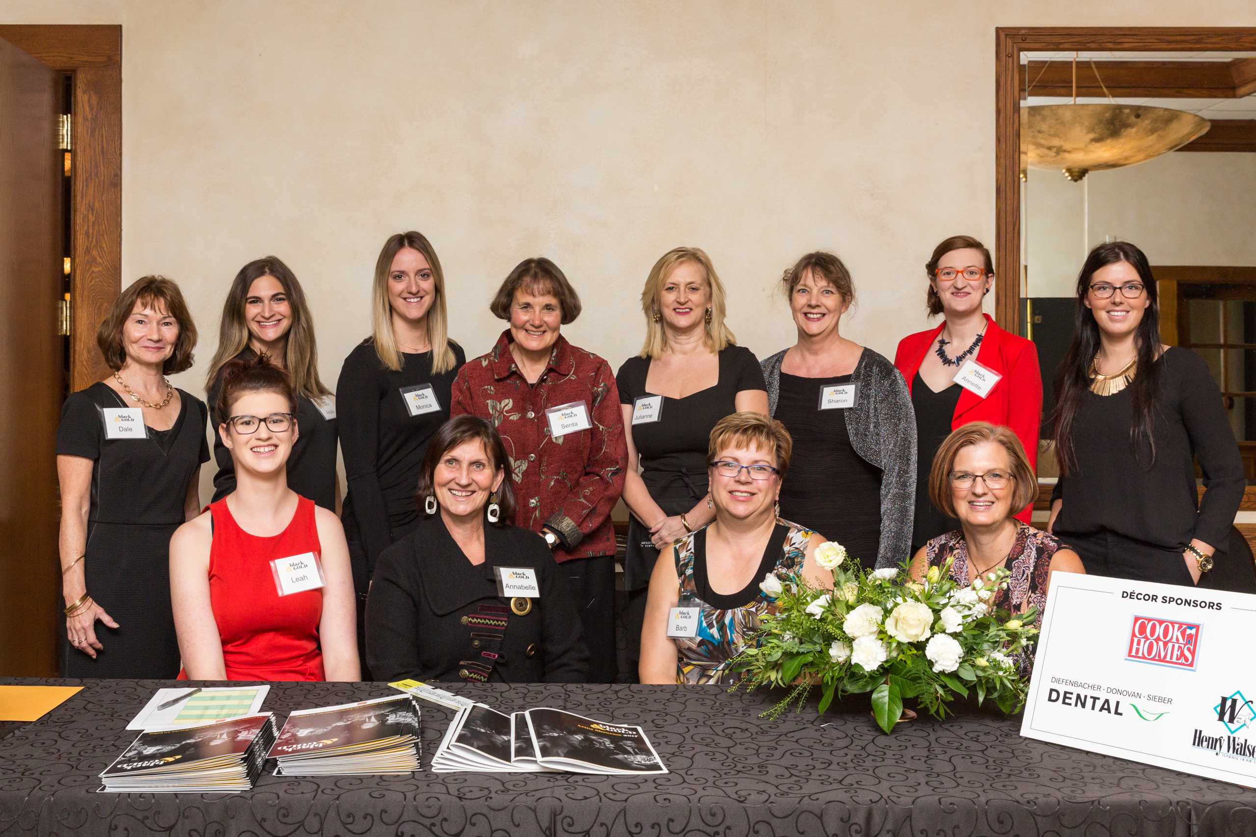 Group photo of KWAG Volunteers at the reception desk of the Black & Gold fundraiser