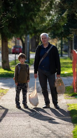 Vertical still image of an older man and his young son on a sidewalk holding a canvas shopping bag between them