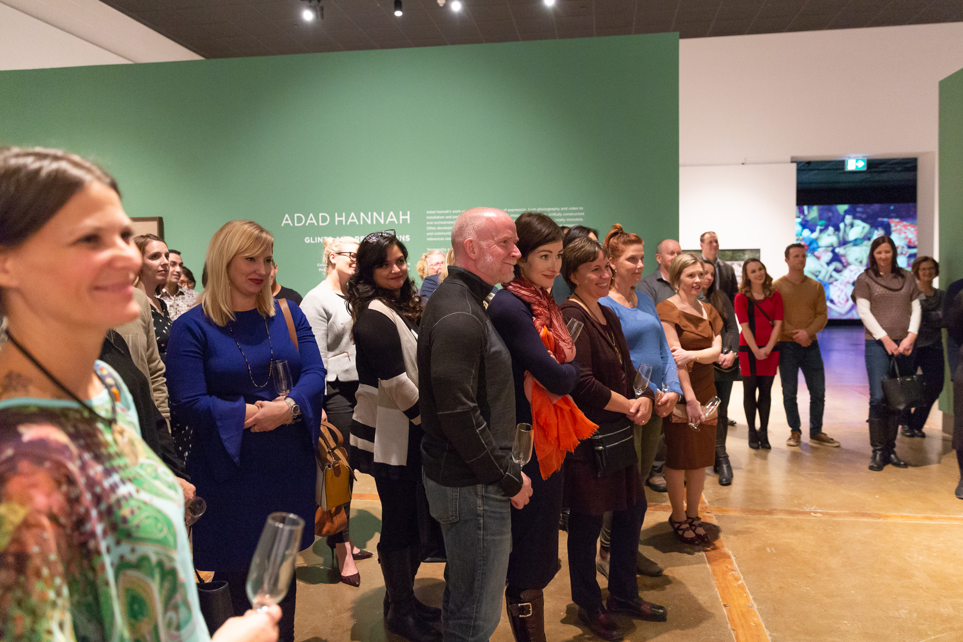 Side view of a large group of smiling people on a guided tour of an Adad Hannah exhibition