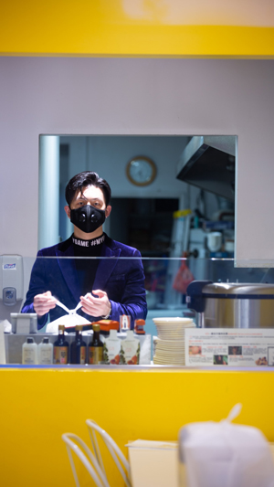 Vertical still image of a take-out restaurant worker in a facemask standing behind a glass counter while tying a white plastic bag