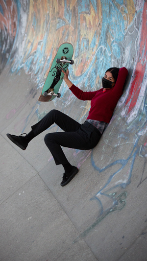 Vertical still image of a female skateboarder in dark clothing and a black facemask holding up her green skateboard while reclined against the side of a graffiti-covered half-pipe